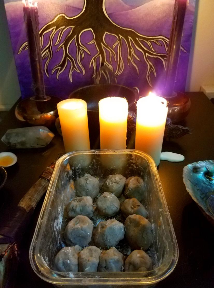 A glass dish of bath bombs on an altar.